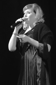 """SINGING FOR LOVE —Tracy Burklund-Becker, Jazz Vocal Ensemble director, sings """"Let's Do it, Let's Fall in Love,"""" making the audience feel the love in the air.   Photo by Karen Tome"""