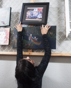 Artist Karina Zuñiga adjusts one of 43 pieces hung in the exhibiton.  Each piece represented one of the 43 students. PHOTO BY April Abarrondo