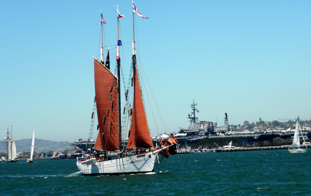Tall ship unfurls her sails as she passes the USS Midway in the San Diego Harbor Festival of Sails. Photo by Marianna Saponara