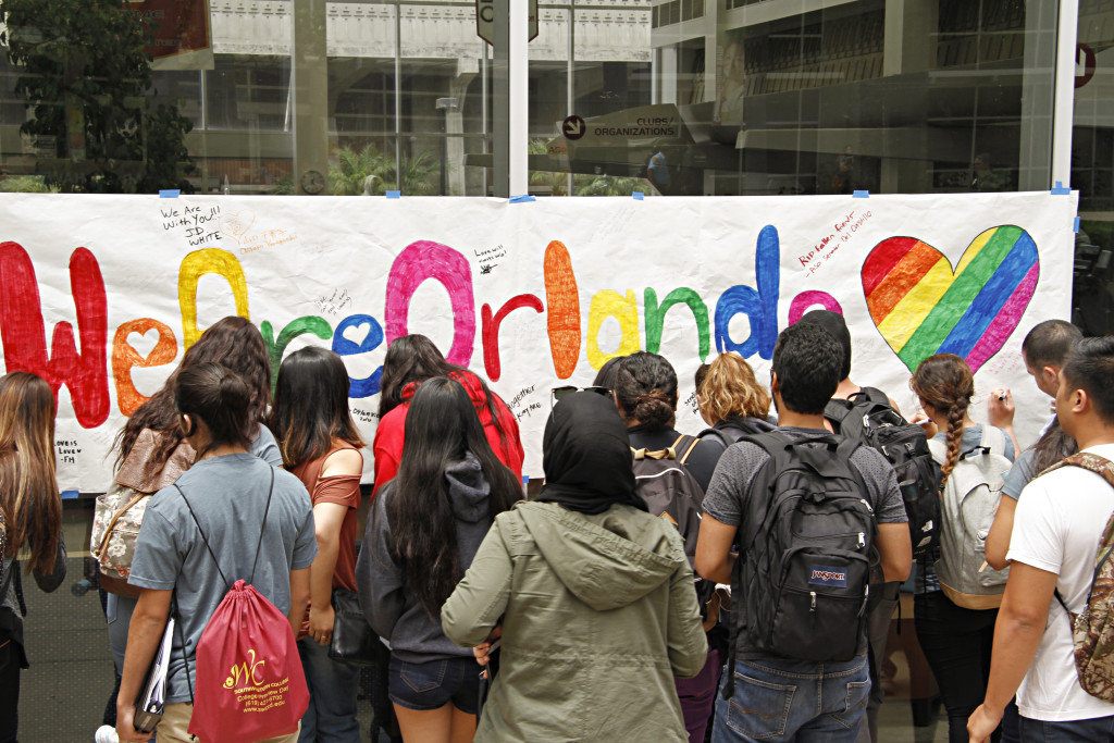 Students crowd around the banner, waiting to sign.