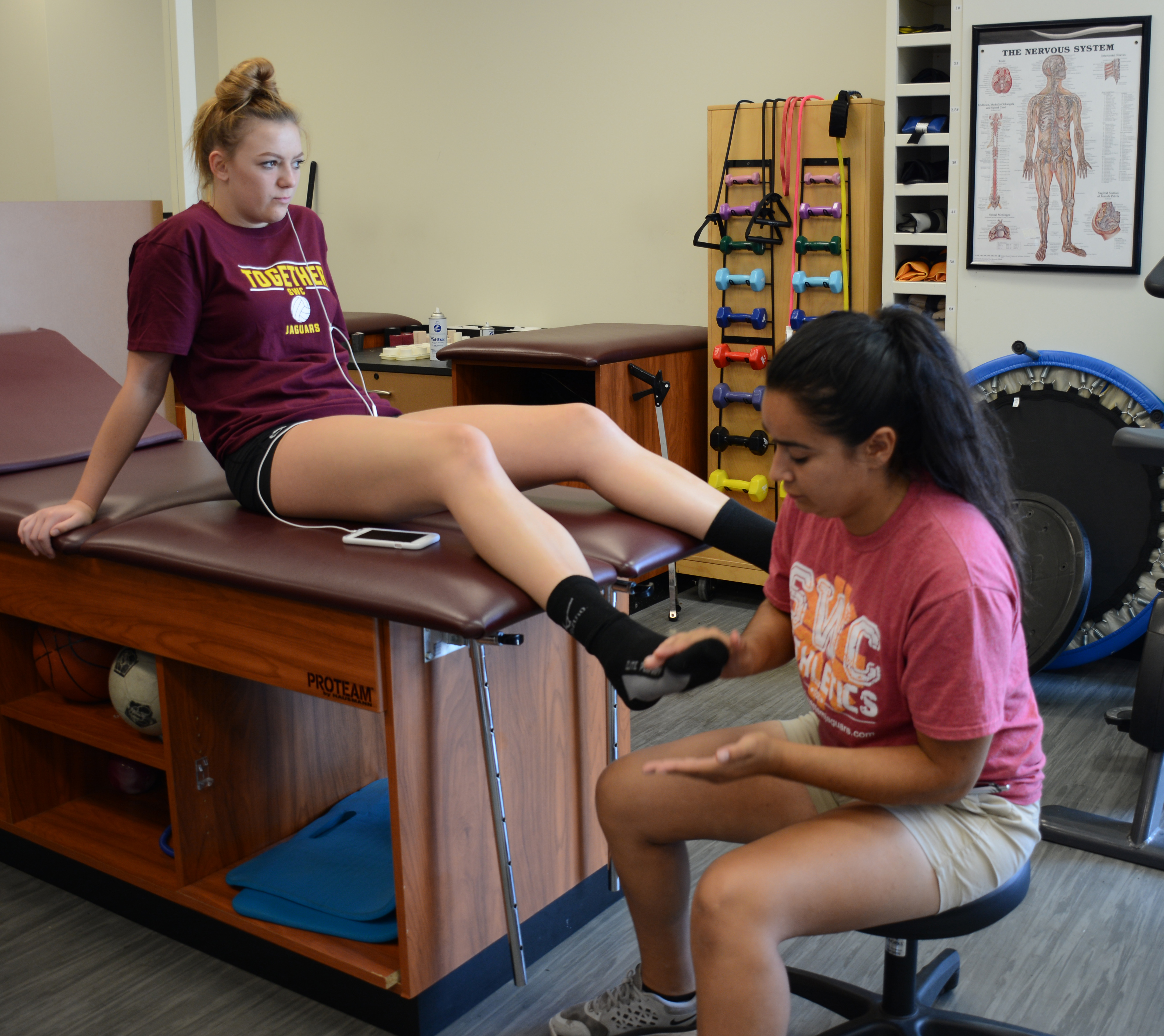Student trainer Edith Herrera tends to volleyball player Carly Threadgill. Photo by Darcy Aguayo